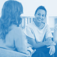 professional counselor woman talking with an adult woman smiling